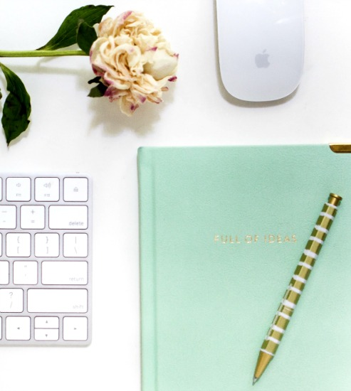 How To Choose a Freelance Writer desk with a keyboard, computer mouse, notebook and pen