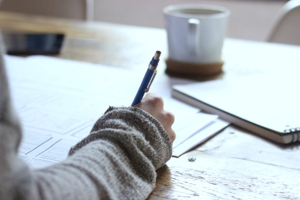 How To Hire A Freelance Writer woman's hand writing something on paper at a desk