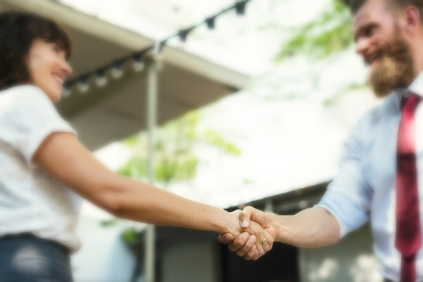 How To Use Networking Tips To Maximize Your Conference Connections For Freelance Work woman and man shaking hands