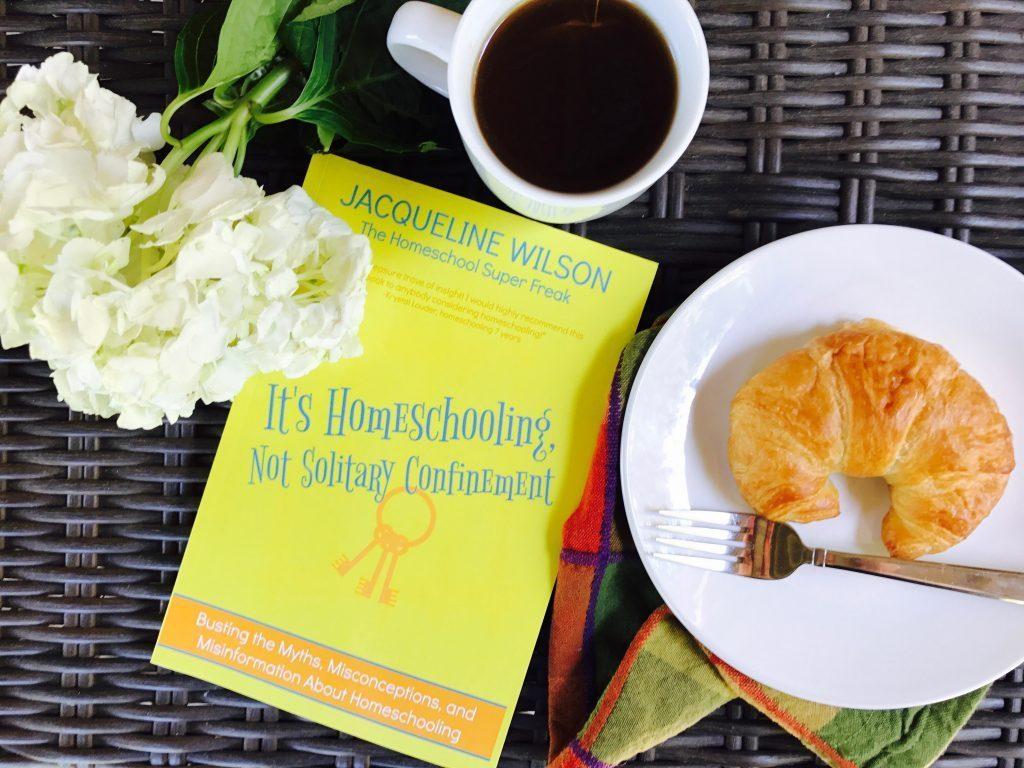 It's Homeschooling Not Solitary Confinement by Jacqueline Wilson book on a tray with a croissant cup of coffee and flowers