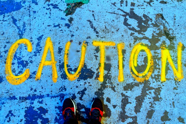 8 Warning Signs To NOT Hire A Freelancer the word caution spray painted on the concrete ground